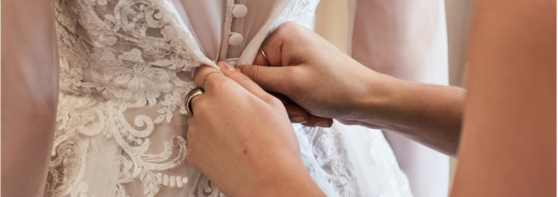 stylist buttoning back of wedding dress