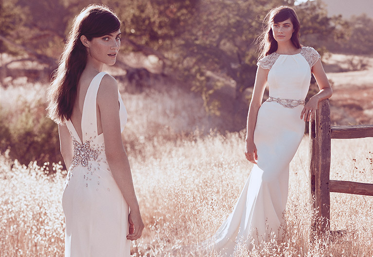 Two brides standing in a field wearing Jenny Packham bridal gowns