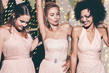 Three bridesmaids dancing in blush gowns