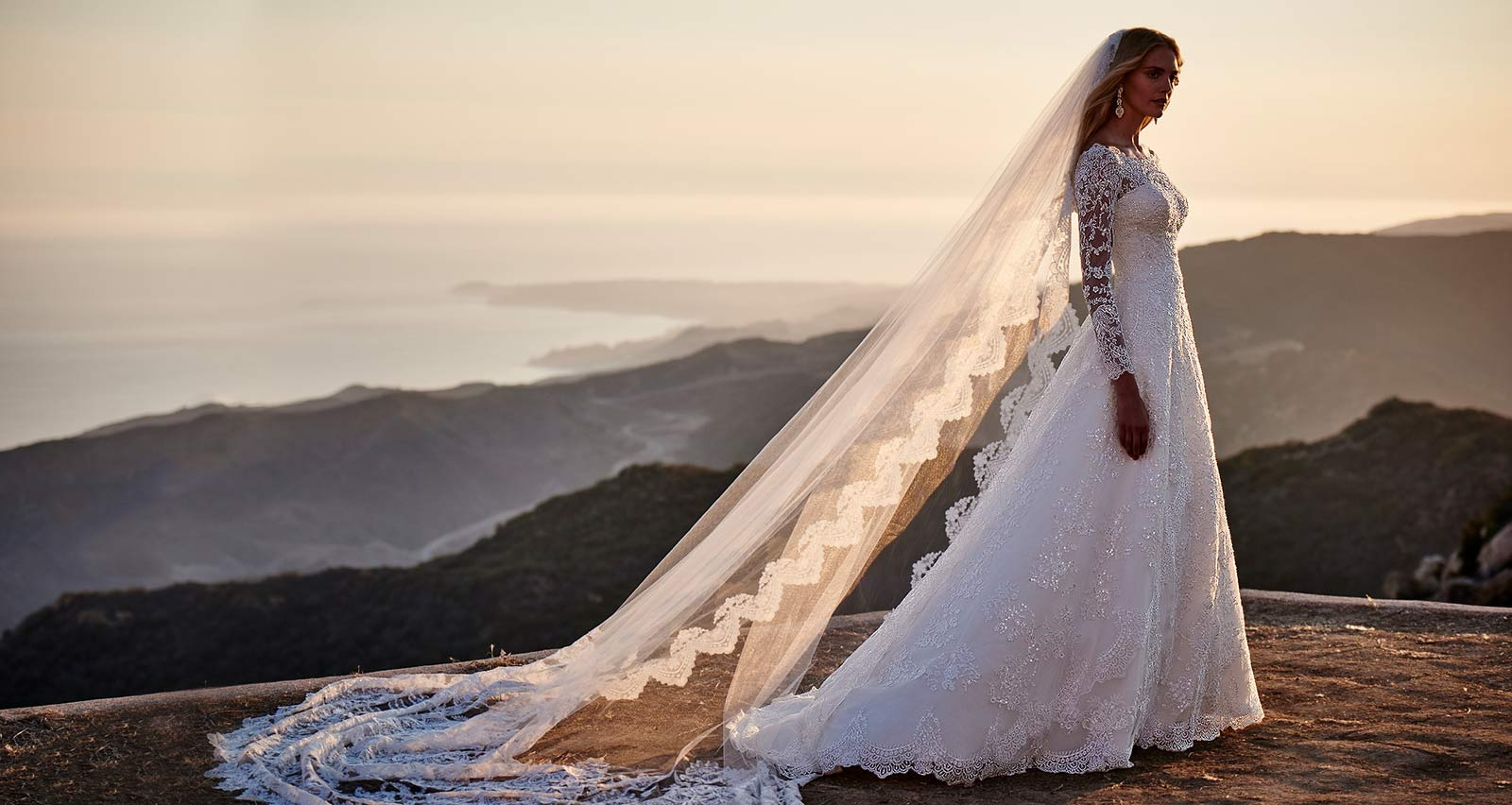 Bride wearing Oleg Cassini wedding gown with veil by the ocean cliff