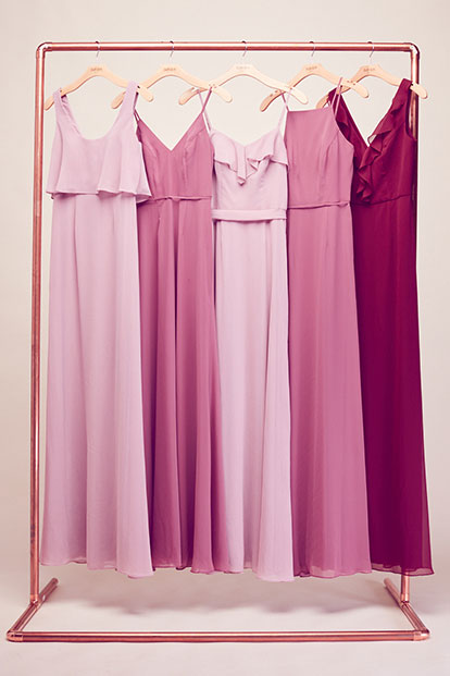 Bridesmaid dresses of varying colors hanging on a rack