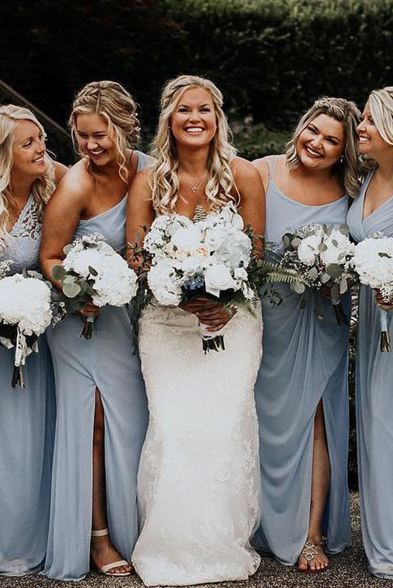 Bridesmaids in blue dresses linking arms with bride