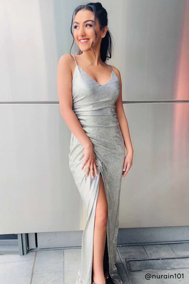 Prom girl wearing silver metallic dress with side slit
