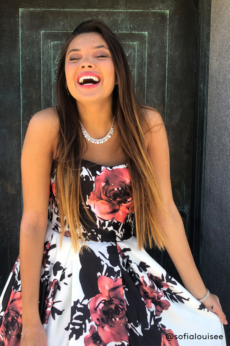 Prom girl laughing while wearing black, white and red floral dress