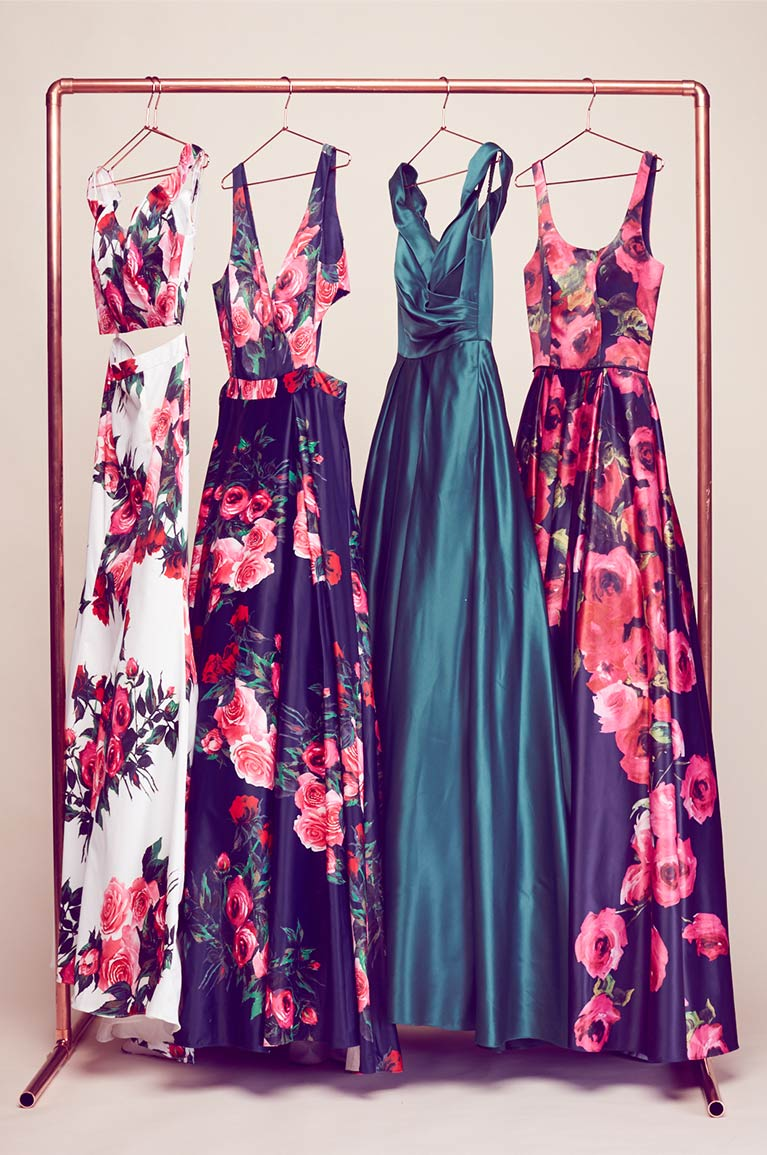 Prom dresses hanging on a rack in varying prints and colors