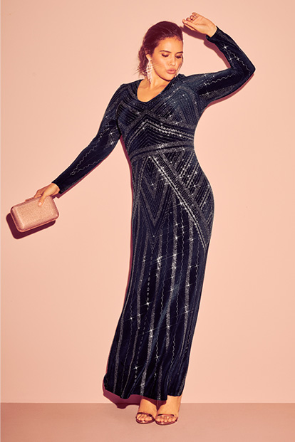Woman wearing long sleeve sparkly holiday dress.