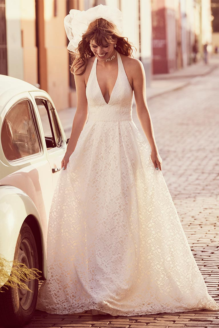 Bride in White Wedding Dress standing next to car
