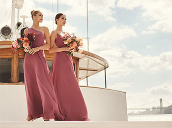 Two bridesmaids wearing coordinating dresses on a boat.
