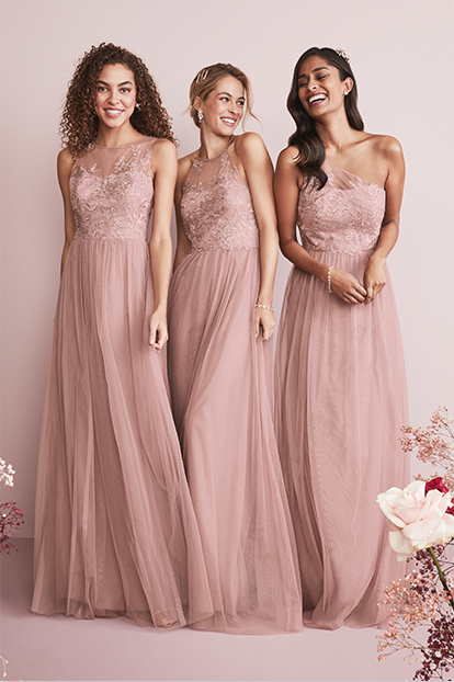 Three bridesmaids wearing long dresses.
