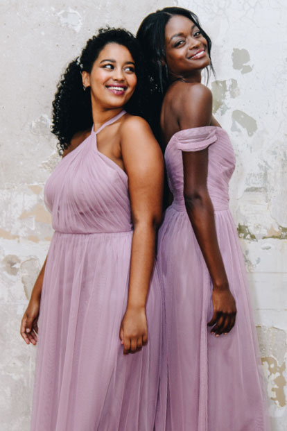 Two bridesmaids wearing lavender haze color dresses.