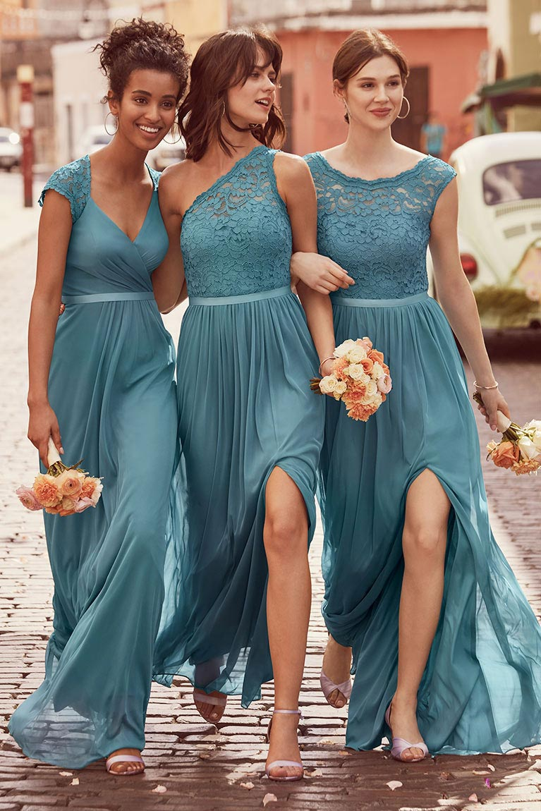 Three Bridesmaids in Teal Blue Dresses Linking Arms Down Street