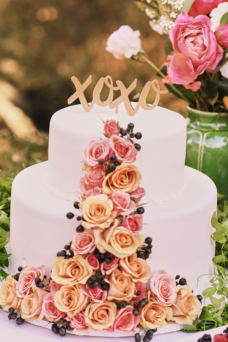XOXO gold cake topper on floral designed wedding cake