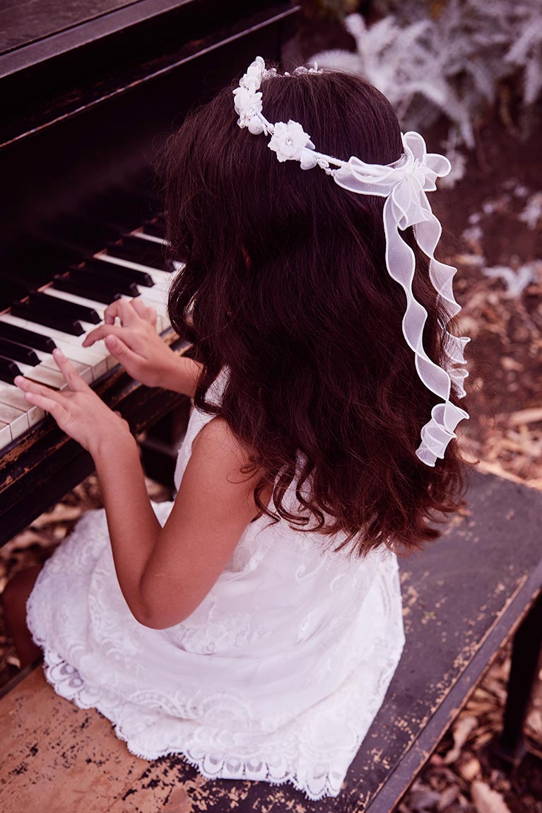 Flower girl with ribbon halo headband playing the piano