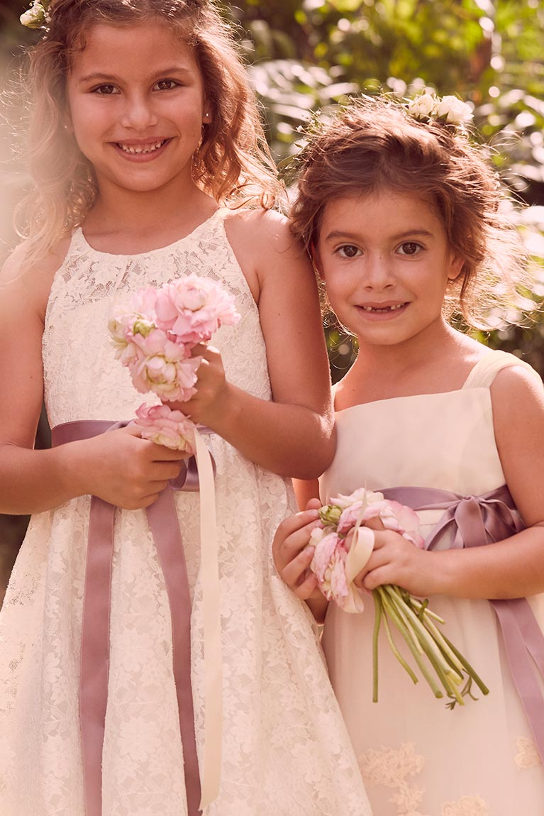 Two flower girls smiling with small bouquets