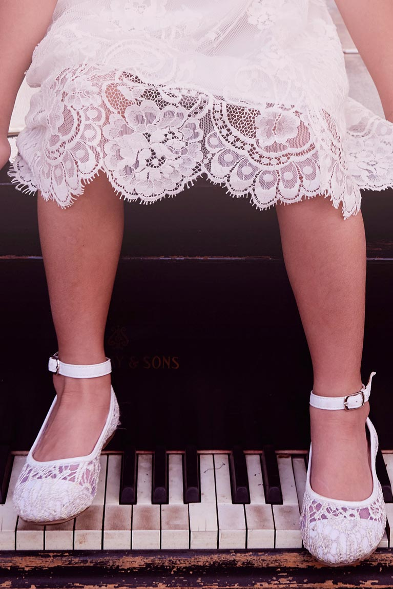Flower girl in lace dress sitting on top of a piano with feet above the keys