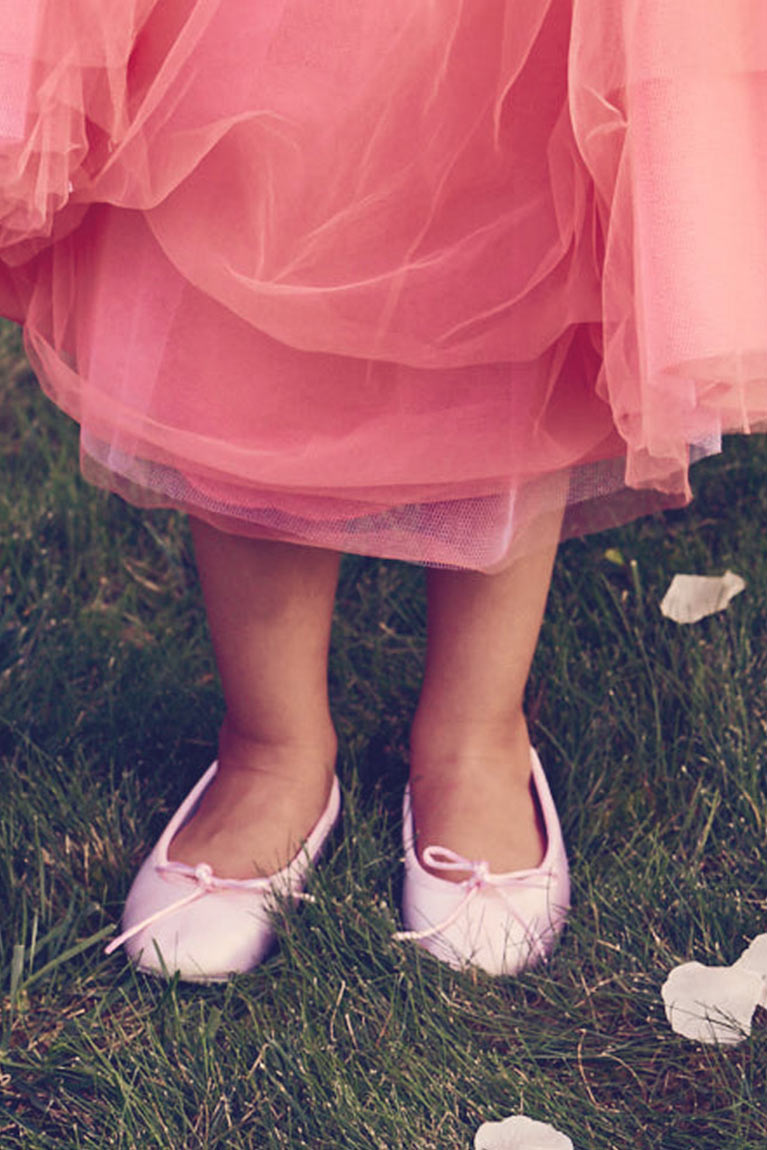Close up with flower girl pink dress and white shoes