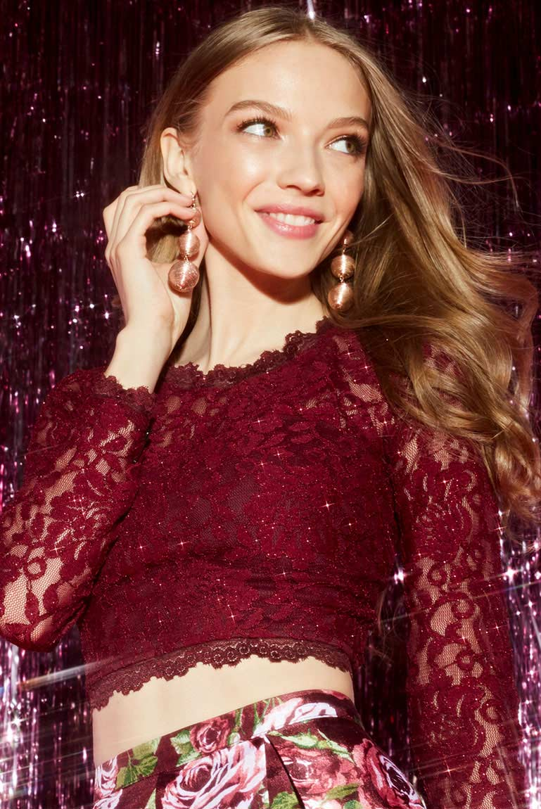 Girl wearing trendy earrings with wine colored homecoming dress.
