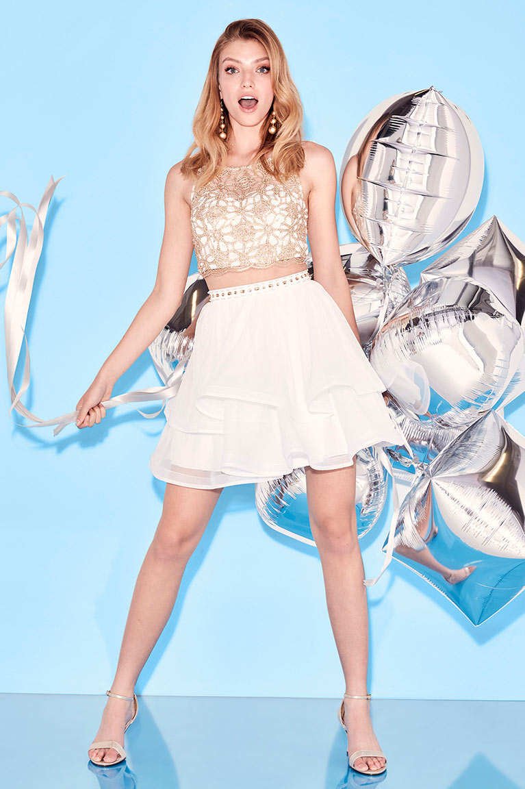 Homecoming girl in white and gold two piece dress holding silver balloons