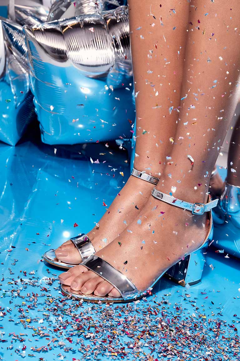 Close up of model wearing silver metallic ankle strap heels with balloons