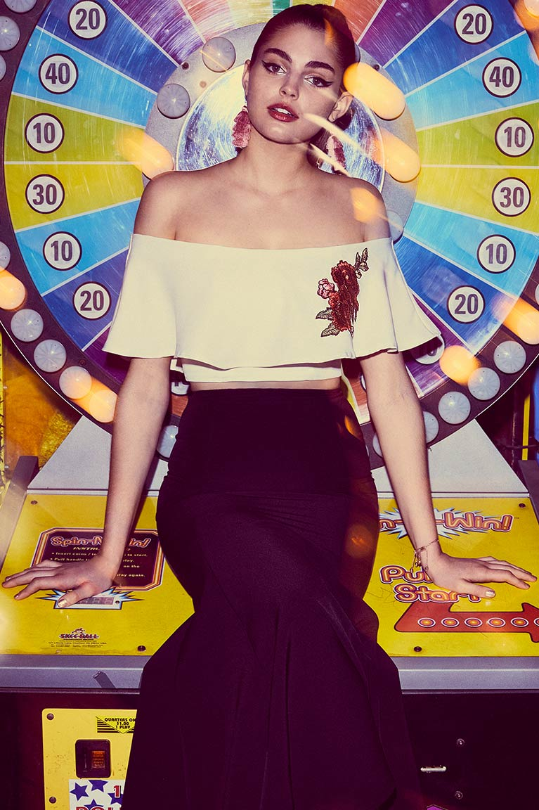 Prom girl in two piece black and white dress sitting on colorful carnival wheel game