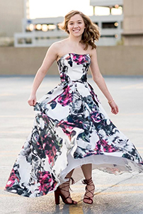 Real prom girl spinning outdoors in black, white and pink floral prom dress