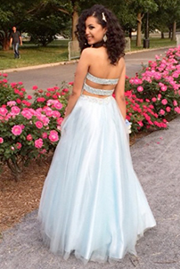 Prom girl looking over her should wearing two piece ball gown prom dress