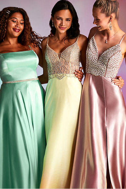 Three girls wearing candy-colored prom dresses.