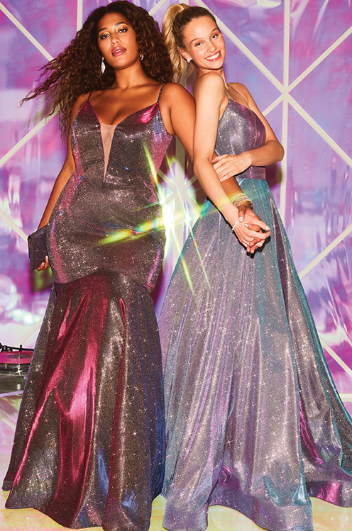 Two girls wearing long metallic prom dresses.