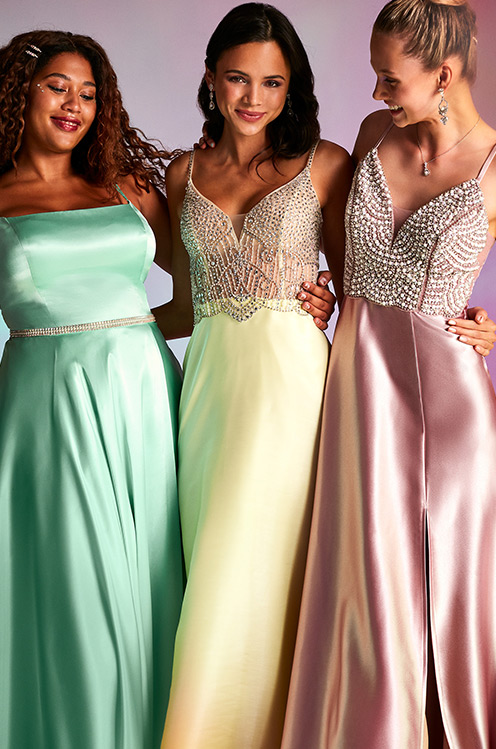Three girls wearing long candy-colored prom dresses.