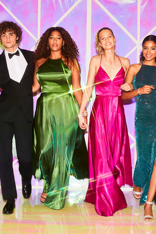 Three girls wearing colorful satin prom dresses.