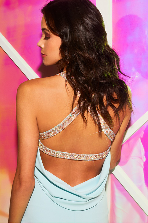 Back of a girl wearing beaded open back prom dress.