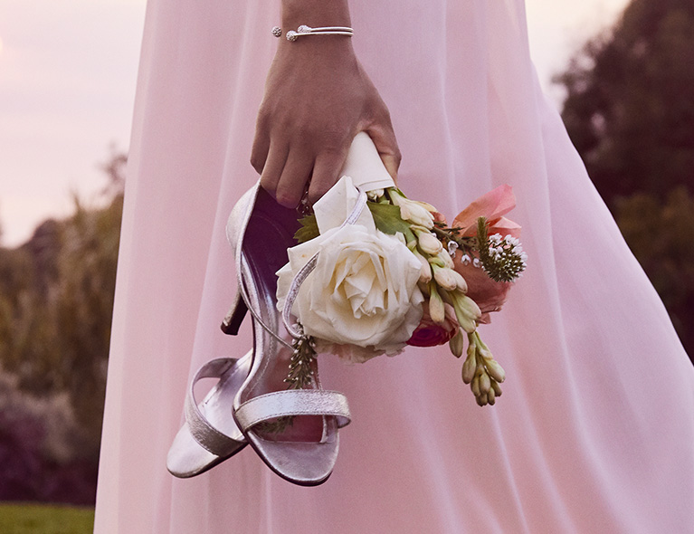 Bridemaid Carrying Silver Evening Shoes & Bouquet