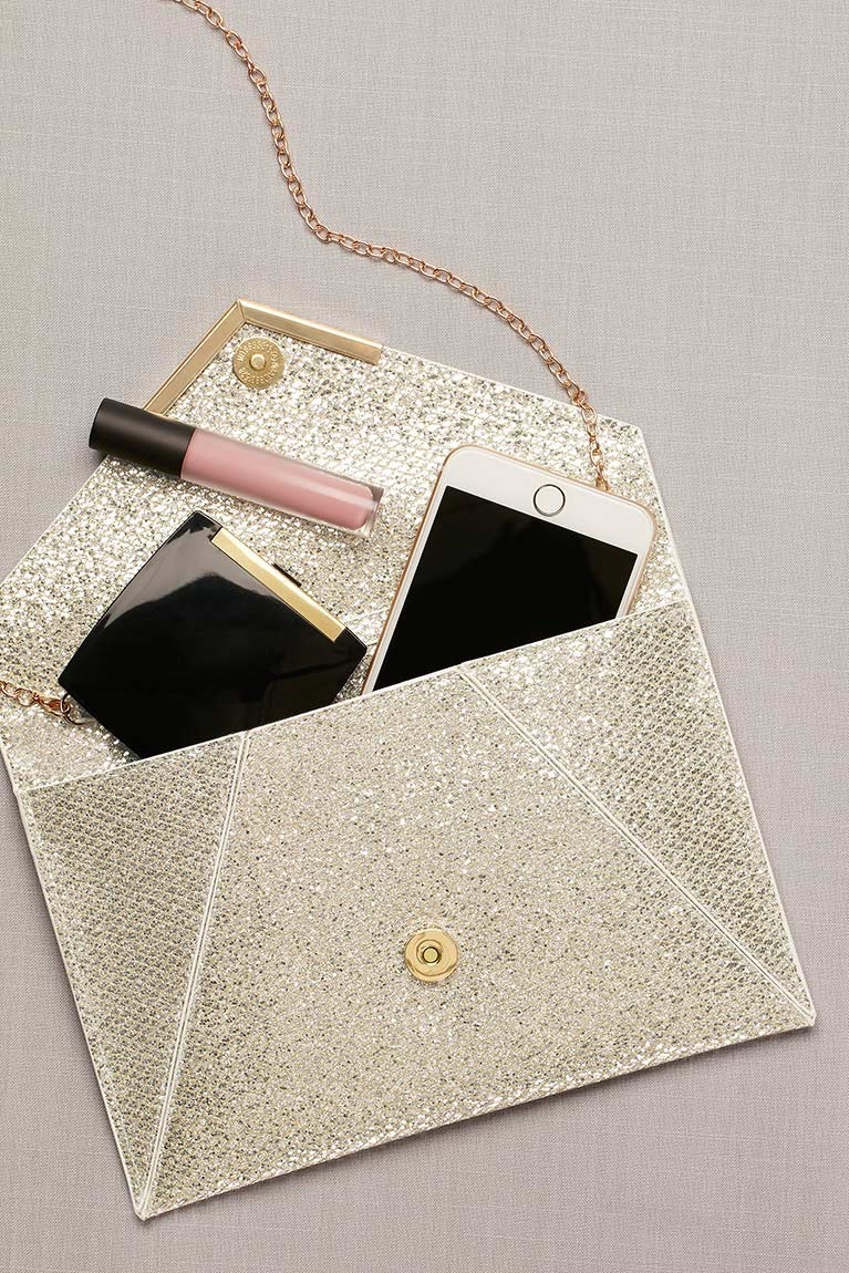 Gold envelope handbag with makeup and a cell phone