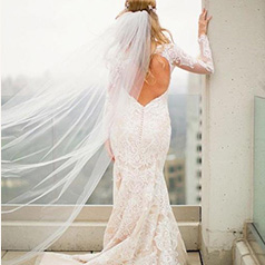 bride standing in long white lace wedding gown with long veil