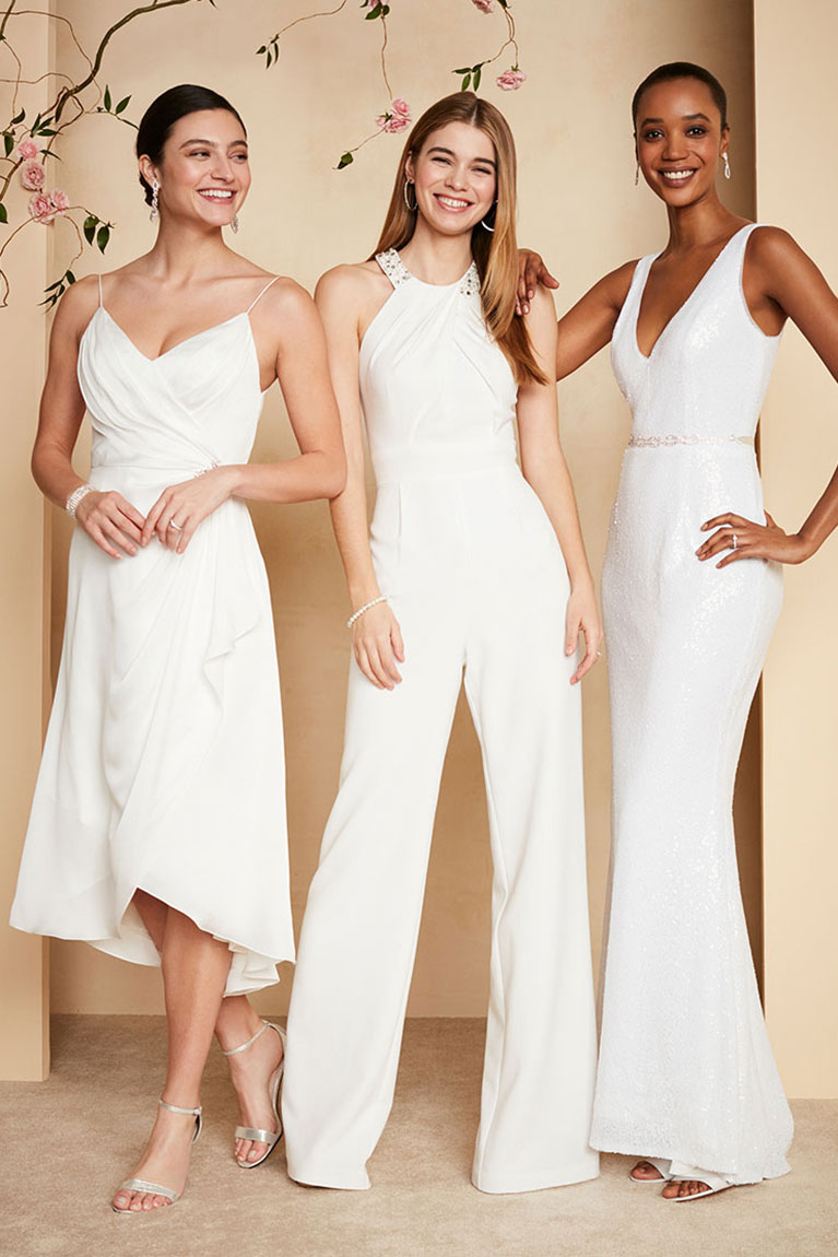 Three women posing together while wearing either a white dress or jumpsuit