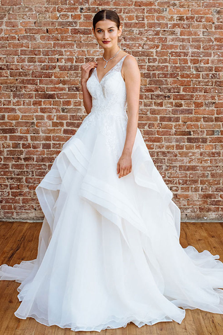 Bride In A Layered Tulle Wedding Dresses Standing In Front Of A Brick Wall