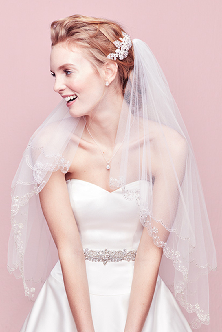 bride wearing crystal crown veil and crystal earrings