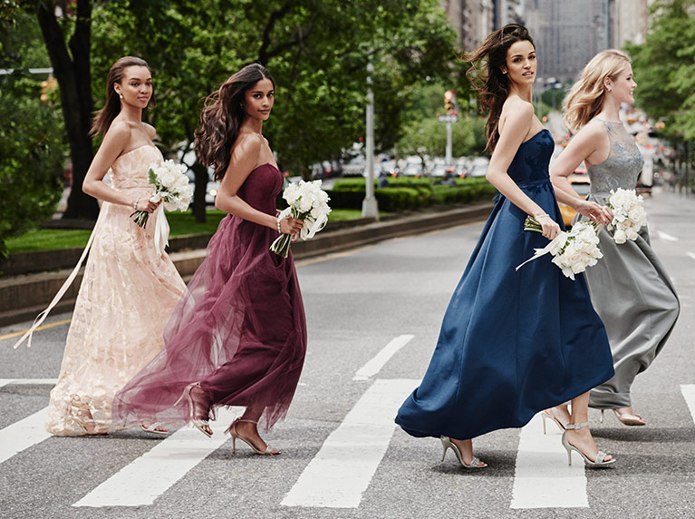 Bridesmaids crossing city street holding bouquets