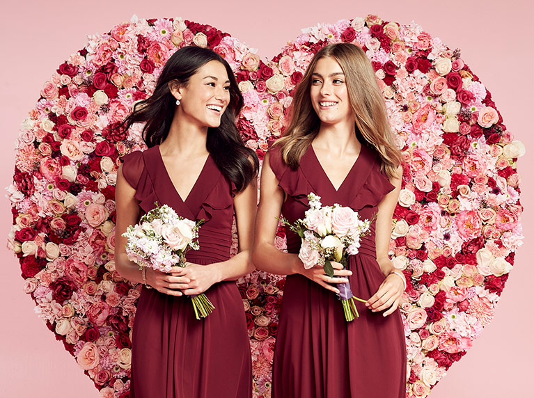 Bridesmaids in red dresses in front of pink flower heart wall