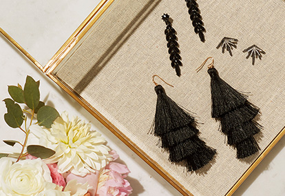 Jewelry tray with black tassel earrings and beaded earrings, and flowers
