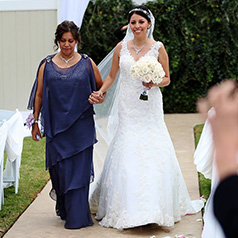 Mother of the bride in purple dress walking her daughter down the aisle