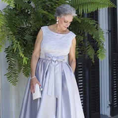 Mother of the bride wearing soft hued ball gown carrying an elegant clutch