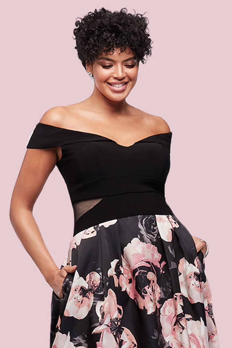 Wedding guest wearing off-the-shoulder dress with black top and floral print bottom