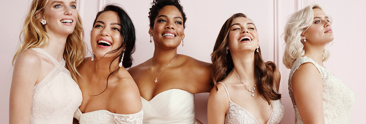 5 brides laughing, wearing a variety of wedding dress styles and sizes