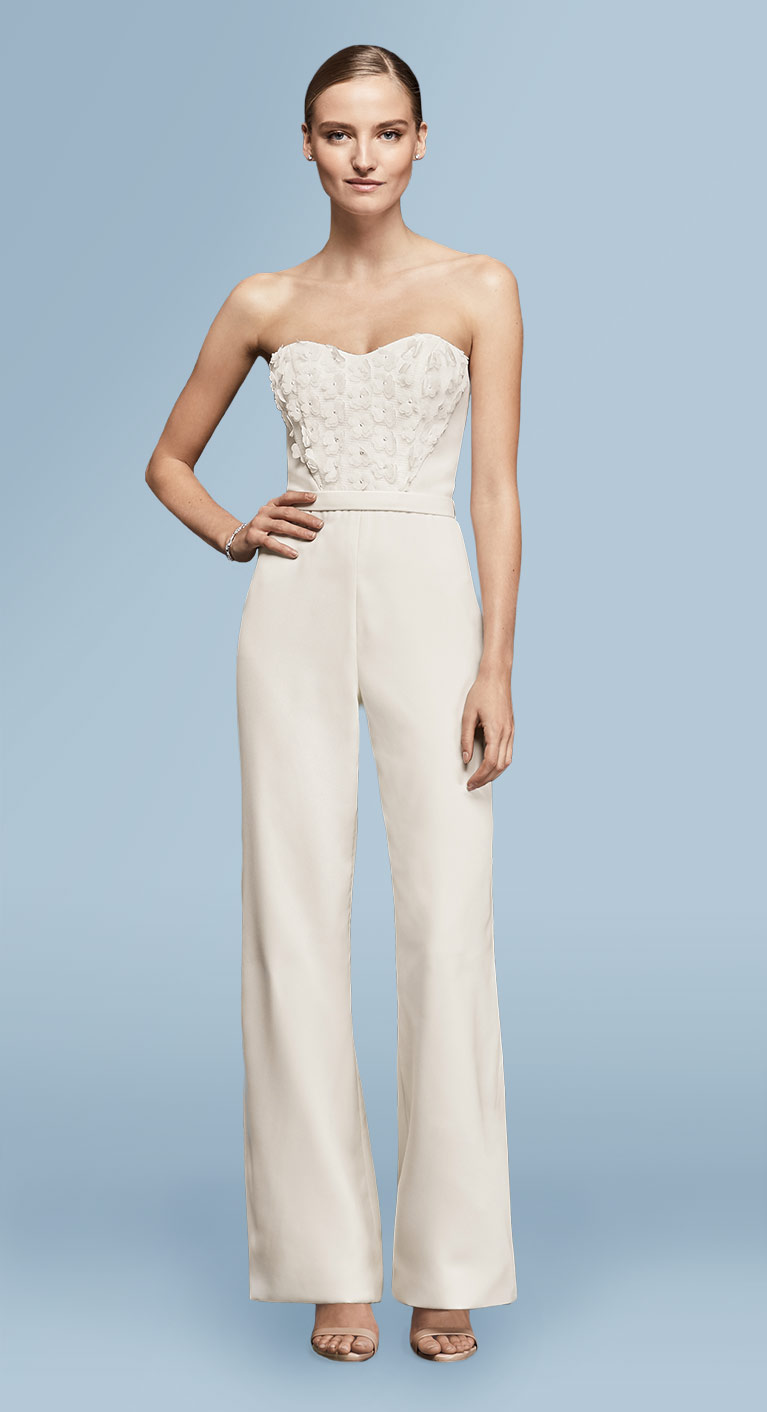 Bride in white jumpsuit with flowers