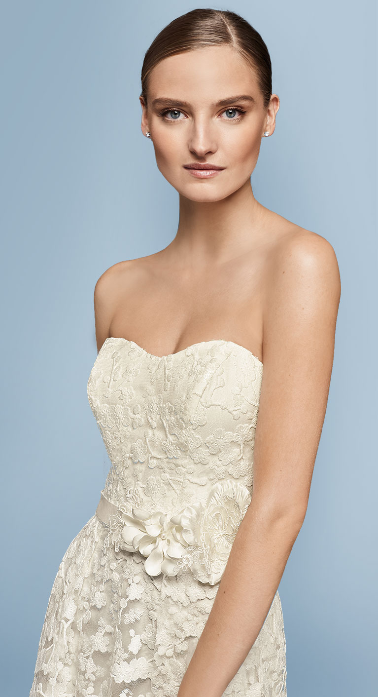 Close up of Bride in strapless lace gown with floral ribbon