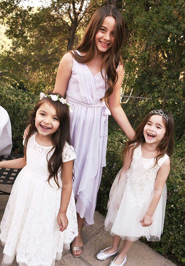 Junior bridesmaid standing with two flower girls outside smiling