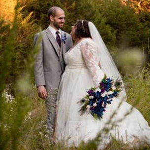 Plus size bride standing with groom in field