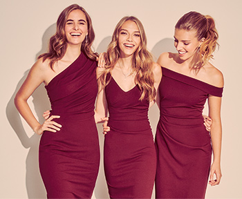 Three bridesmaids in wine colored dresses smiling and laughing