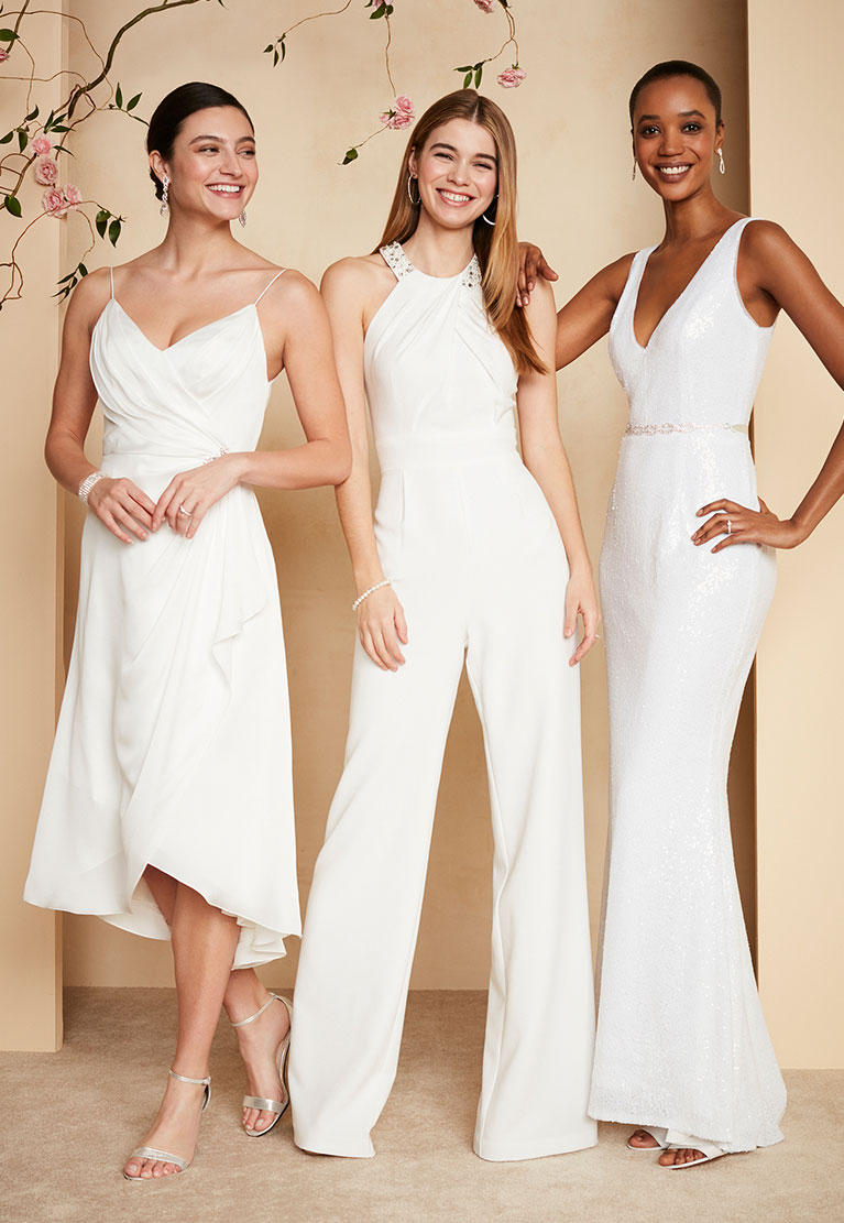 Db studio wedding dress collection davids bridal three women in various wedding dresses and jumpsuit smiling with floral tree branch in background ombrellifo Gallery